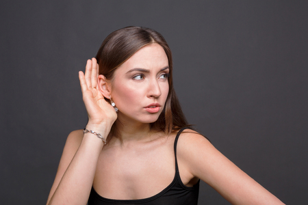Young woman trying to listen gossip. Very curious girl holding her hand near ear, trying to hear something Stock Photo
