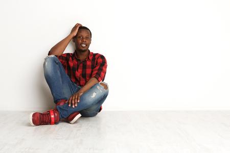 Happy smiling black man sitting legs crossed, hand near head, at white studio background, man style