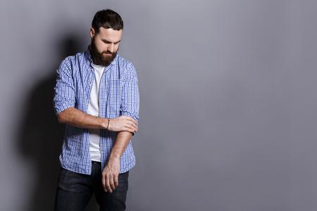 Bearded man preparing to work hard, adjusting sleeves, copy space, gray studio background