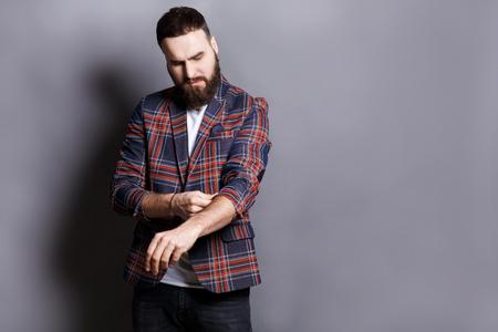 Bearded man in checkered jacket preparing to work hard, adjusting sleeves, copy space, gray studio background