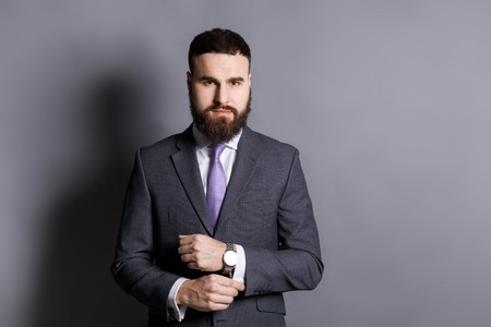 Handsome young bearded man in suit adjusting sleeves. Confident stylish businessman ready for meeting, copy space, gray studio background