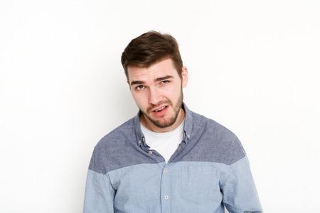 Homme cochonne grimaçant, portrait. Portrait de jeune homme audacieux avec look impertinent, isolé sur fond blanc Banque d'images - 81478285