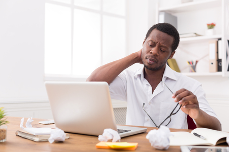 Overworked african-american employee in office. Tired and having neck pain while working on laptop on new project