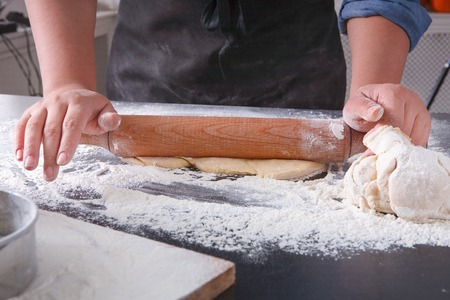 pin board: Baking concept. Hands roll dough on black kitchen table. Baker cooking pastry Stock Photo