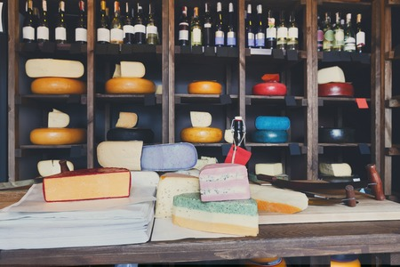store shelf: Grocery shop interior. Cheese wheels arranged on wooden shelves, coloured cheese and wrapping paper on counter and wine assortment, background