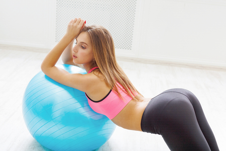 fitball: Young woman doing fitness exercises with fit ball at gym. Stock Photo