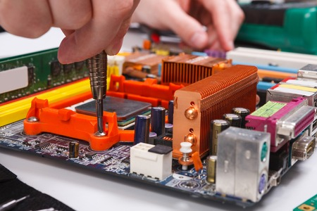 Engineer checking motherboard with multi-meter close up. Stock Photo
