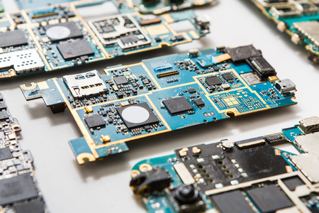 disassembly: Digital gadgets components, repair shop concept. Motherboards of disassembled smartphones on service center workplace. Stock Photo
