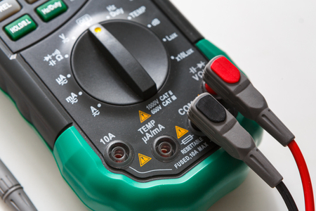probes: Digital multimeter with switch and wires. Measurement electrician tool closeup on white background Stock Photo