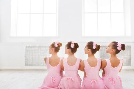 Little ballerinas in ballet studio. Group of girls having break in practice, sitting on floor, back view. Classical dance school Stock fotó