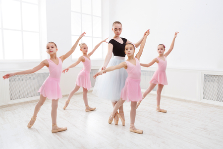 Young ballet teacher and students ballerinas in dance class. Girls are engaged in choreography in the ballet school.