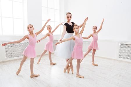 Jonge ballet leraar en studenten ballerina's in dans klasse. Meisjes zijn bezig met choreografie in de balletschool.