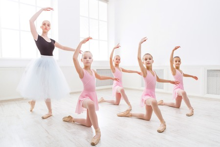 Young ballet teacher and students ballerinas in choreography class of ballet school.