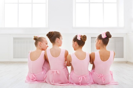 Little ballerinas talking in ballet studio. Group of girls having break in practice, sitting on floor, back view. Classical dance school