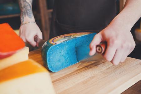 Cutting gouda pesto lavender, blue cheese in grocery shop, closeup Stock Photo