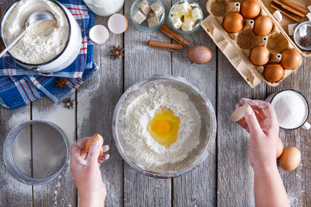 hand brake: Making dough top view. Overhead of baker hands with broken eggshell. Eggs and flour in a bowl. Cooking ingredients for pastry on rustic wood, culinary classes or recipe concept. Stock Photo