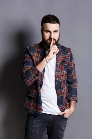 rumour: Bearded man shows hush be quiet. Handsome hipster holding finger at his lips, gray studio background, copy space. Secret, privacy concept