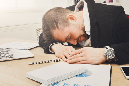 Young tired businessman sleeping in office near laptop. Exhausted employee. Lifestyle portrait