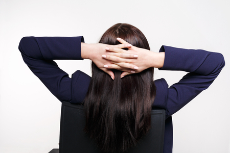 Relaxed businesswoman portrait back view. Young woman in business style with hands crossed behind her head isolated on white background Stock Photo