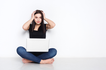 shocking: Schocking news. Worried woman sitting at home on floor and looking on screen of laptop while holding hands on her head. Stock Photo
