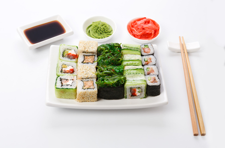 Traditional japanese food restaurant. Sushi set on white plate, soy sauce, ginger, wasabi and chopsticks aside. Colorful rolls and gunkan assortment at white background, pov Stock Photo