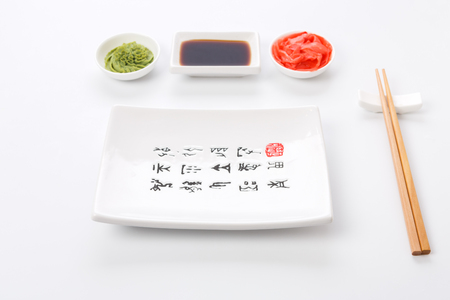 Set of sushi tablewear. Empty rectangular sushi plate with hieroglyphs, saucer, ginger, wasabi and chopsticks at white background. Flat lay, copy space