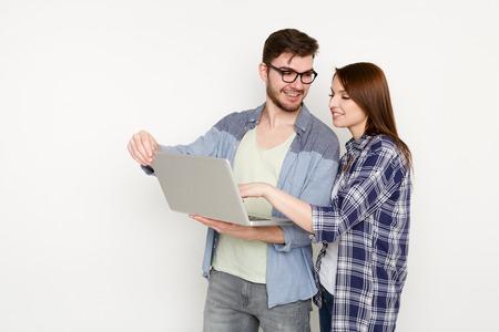 Paargesprek met laptop. Vrouw die nieuwe kleding tonen aan de mens op computer, glimlacht hij in goedkeuring, witte achtergrond, studioschot Stockfoto