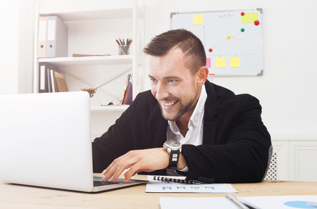 irresponsible: Gambling or gaming in the office. Excited young Businessman addicted to computer. Happy man looks at laptop screen, internet leisure at work