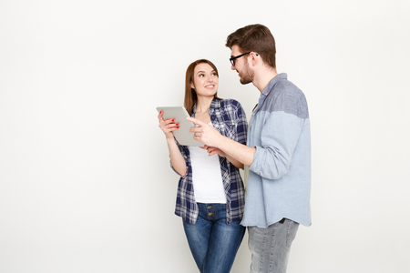 Couple conversation with tablet. Man showing project to woman on digital tablet, white background, studio shot Stock Photo