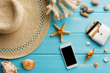 Vacation background on blue wood, top view with copy space. Seashells and straw hat. Booking tickets on smartphone