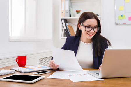 Paperwork. Smiling business woman in formal wear sitting at wooden desk in modern office and reading report document.