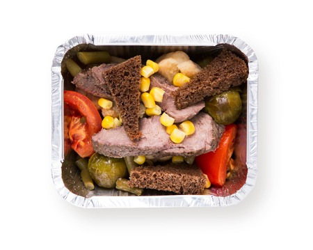 foil: Healthy food in foil box isolated at white background. Daily slimming menu. Organic restaurant food take away and delivery. Steamed meat with vegetable salad, rye bread and corn, top view