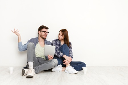 Couple discuss something with tablet in hand. Happy man and woman sitting on the floor in white interior of their new apartment Reklamní fotografie
