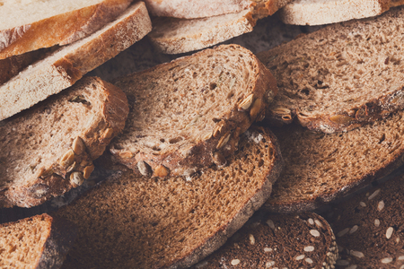 sprinkled: Sliced bread gradient background. Bakery and grocery concept. Fresh, healthy whole grain sliced sorts of rye and white loaves on wood