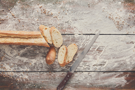sprinkled: Bakery and grocery background. Cutting baguette, top view on rustic wood Stock Photo