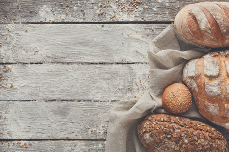 sprinkled: Bread frame on rustic wood background, copy space. Brown and white loaves and flour still life composition with wheat flour sprinkled around.