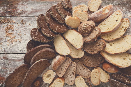 sprinkled: Sliced bread background on rustic wood, copy space. Brown and white loaves and flour top view composition with wheat flour sprinkled around. Stock Photo