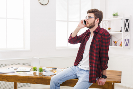 Happy, young and relaxed businessman in casual using phone in modern workplace interior. Stock Photo