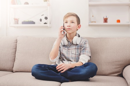 living room interior: Teenager talking on mobile. Phone call distracted boy from listening to music at home. Stylish kid in checkered shirt and jeans with headphones on the neck chatting with friend