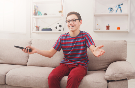 changing channel: Favorite TV show. Teenager with remote panel watching TV while sitting on the couch in living room at home Stock Photo