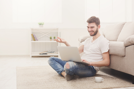 Young man having video call on laptop. Boy in casual talking, smiling and gesturing on the floor in light appartment, copy space Stock Photo