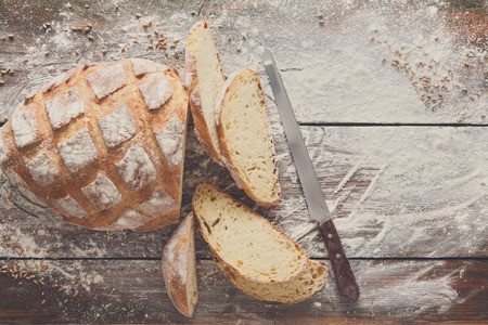 cutting: Bakery and grocery background. Cutting baguette, top view on rustic wood Stock Photo