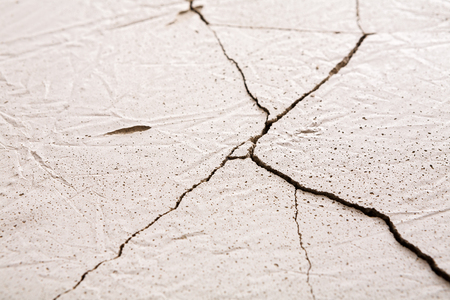 Fractured white concrete background. Old cracked plaster floor top view, copy space Stock Photo