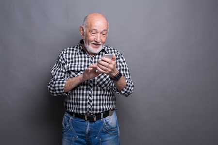 Vrolijk hoger mens het typen bericht op smartphone, die zijn mobiele telefoon, grijze studioachtergrond met behulp van. Communicatie concept Stockfoto