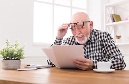 Vrolijke senior man op zoek naar foto's, zittend aan tafel, kopie ruimte. Goede herinneringen concept
