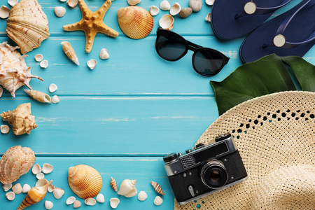 Vacation vintage background on blue wood, top view with copy space. Beach accessories, flip flops, sunglasses, retro photo camera and seashells