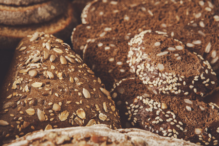 Rye bread background, closeup of sliced loaves on black Stock Photo