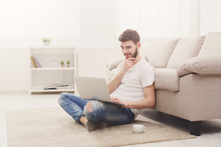 Young man reading on laptop. Boy in casual sitting on the floor in light appartment, copy space Stock Photo