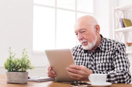Senior man reading news on digital tablet. Serious mature male using portable computer at home, sitting at table, copy space