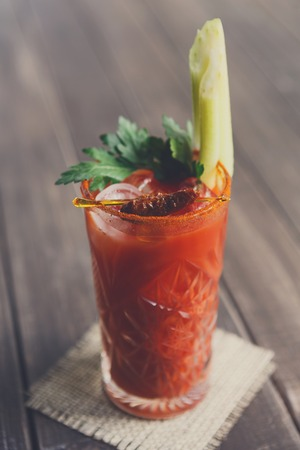 Bloody mary cocktail, vodka and tomato juice in glass on wooden table closeup. Stock Photo